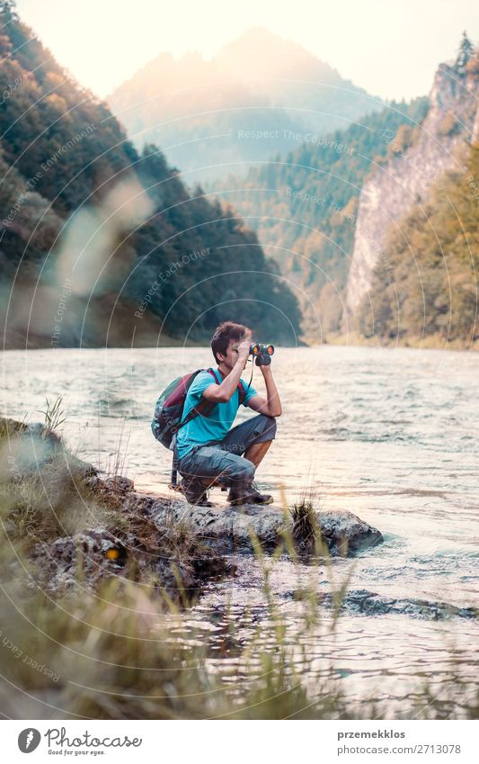 Young tourist with backpack looks through a binoculars Lifestyle Leisure and hobbies Vacation & Travel Trip Summer Mountain Human being Boy (child) Young man