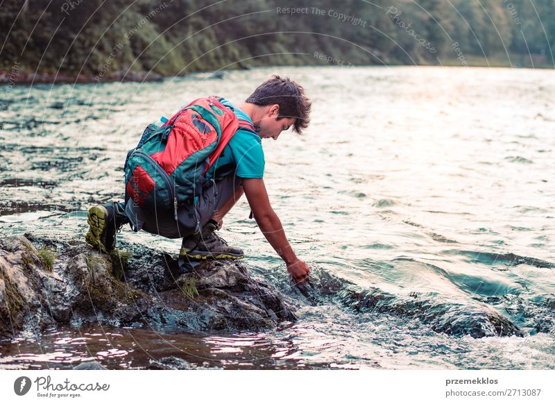 Young boy with backpack sitting on rock over a river Lifestyle Body Leisure and hobbies Vacation & Travel Trip Summer Human being Boy (child) Young man