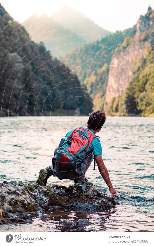 Young boy with backpack sitting on rock over a river Lifestyle Body Leisure and hobbies Vacation & Travel Trip Summer Mountain Human being Boy (child) Young man