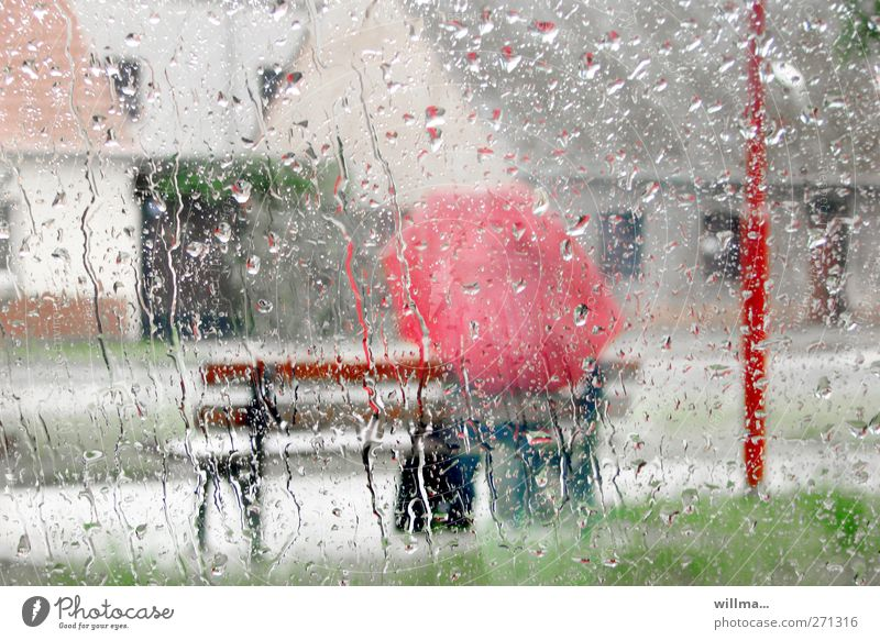 Human being Red Loneliness Sadness Rain Weather Gloomy Glass Sit Wait Drops of water Individual Wet Sidewalk Bench Village