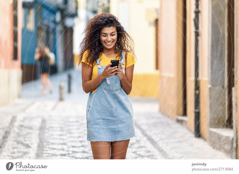 African woman walking on the street looking at her smart phone Woman Human being Youth (Young adults) Young woman Beautiful Joy Black 18 - 30 years Street
