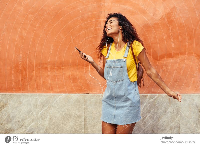 Young Arab woman listening to music with earphones outdoors Woman Human being Youth (Young adults) Young woman Beautiful Joy Black 18 - 30 years Street