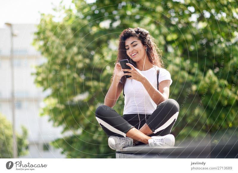 African woman listening to music with earphones and smart phone Lifestyle Style Happy Beautiful Hair and hairstyles Music Sports Telephone PDA Technology