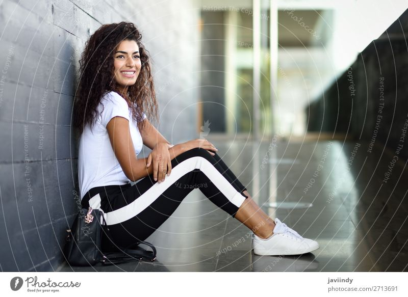 African woman with black curly hairstyle sitting on urban floor. Lifestyle Style Happy Beautiful Hair and hairstyles Face Sports Human being Feminine