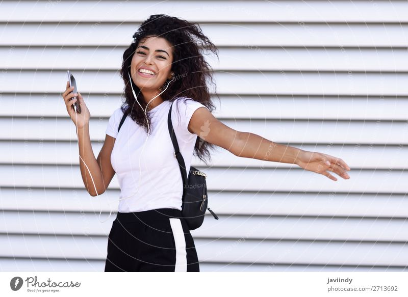 African woman listening to music with earphones and smartphone Woman Human being Youth (Young adults) Beautiful Joy 18 - 30 years Street Adults Feminine Sports