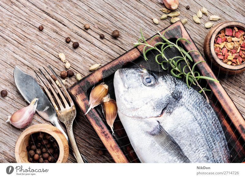 Raw fresh dorado fish uncooked food seafood healthy raw ingredient table lemon cooking diet rosemary mediterranean board preparation cuisine herb pepper wooden