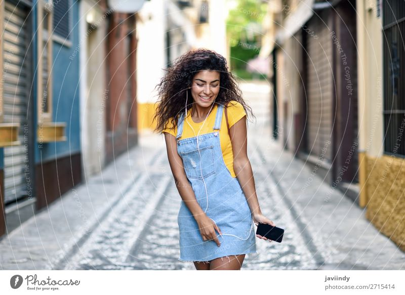 Young Arab woman listening to music with earphones outdoors Lifestyle Style Happy Beautiful Hair and hairstyles Music Telephone PDA Technology Human being