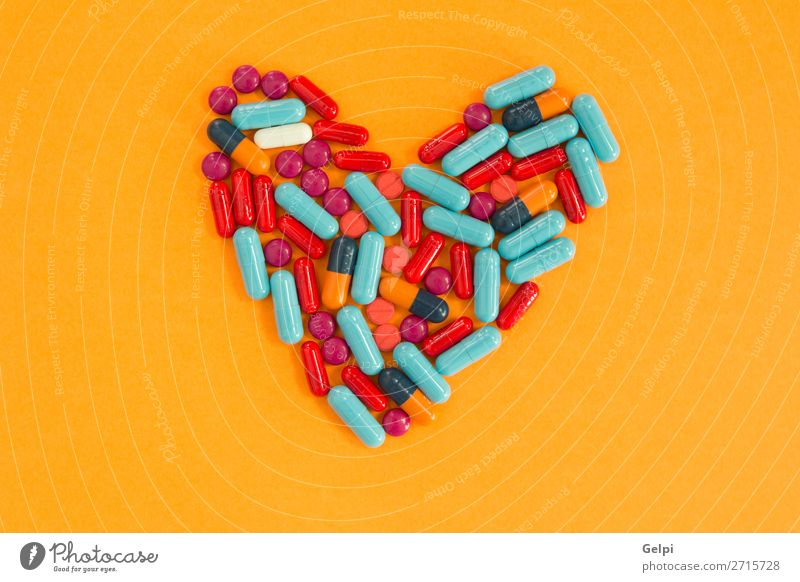 Pills arranged in heart shape on an orange background Blue White Health care Copy Space Heart Illness Medication Pain Science & Research Bottle Vitamin Hospital