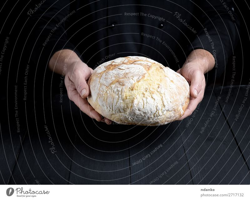male chef hands hold a whole loaf of baked round bread Bread Nutrition Table Kitchen Cook Human being Man Adults Hand Wood Make Dark Fresh Brown Black White