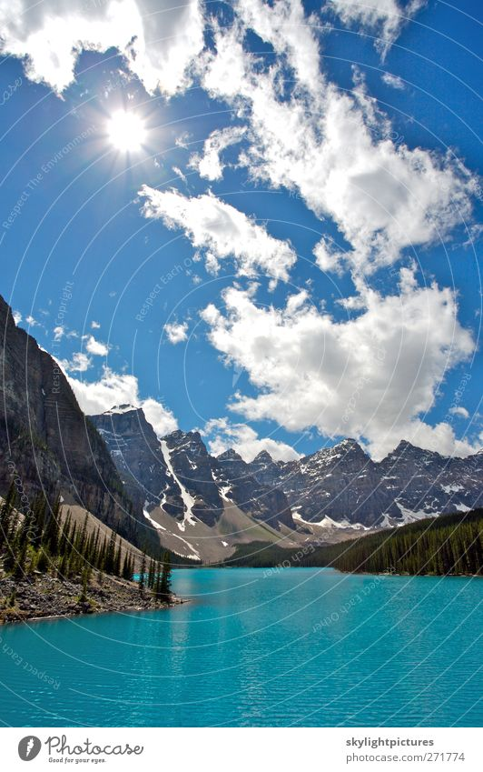 Summer day at beautiful Moraine Lake Tourism Sightseeing Sun Waves Mountain Hiking Nature Landscape Sky Clouds Beautiful weather Tree Forest Peak