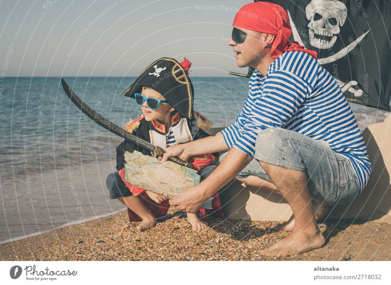 Father and son playing on the beach at the day time. They are dressed in sailor's vests and pirate costumes. Concept of happy game on vacation and friendly family.