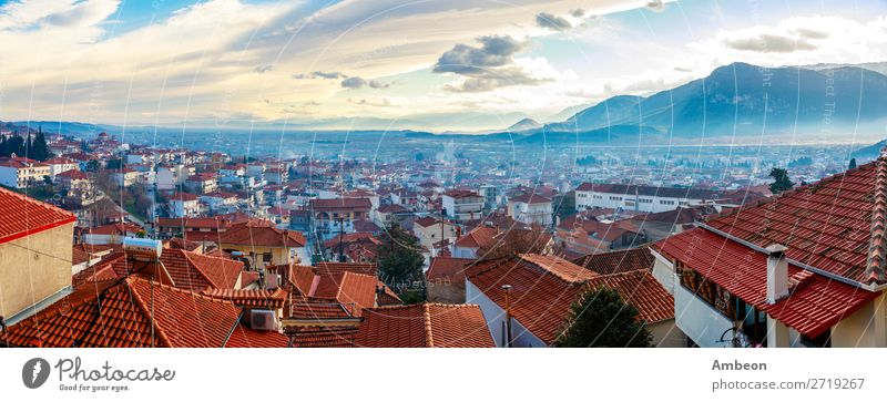 Greek town evening panorama with red roof houses in the valley with sunset mountains, Kalabaka, Thessaly, Greece autumn beautiful building church cityscape