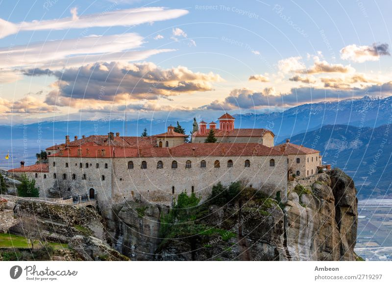 Agios Stephanos or Saint Stephen monastery located on the huge rock with mountains and town landscape in the background, Meteors, Trikala, Thessaly, Greece