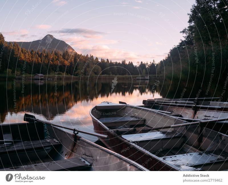 Few boats on shore of lake in Dolomites, Italy Watercraft Coast Lake Mountain Serene Landscape