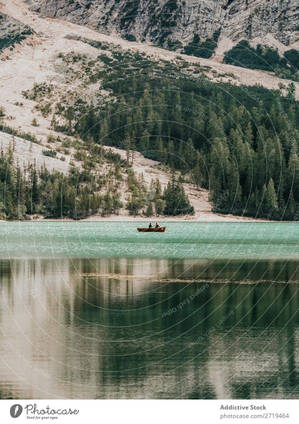 People in boat floating in lake Human being Watercraft Lake Mountain Adventure Trip Exterior shot Relaxation