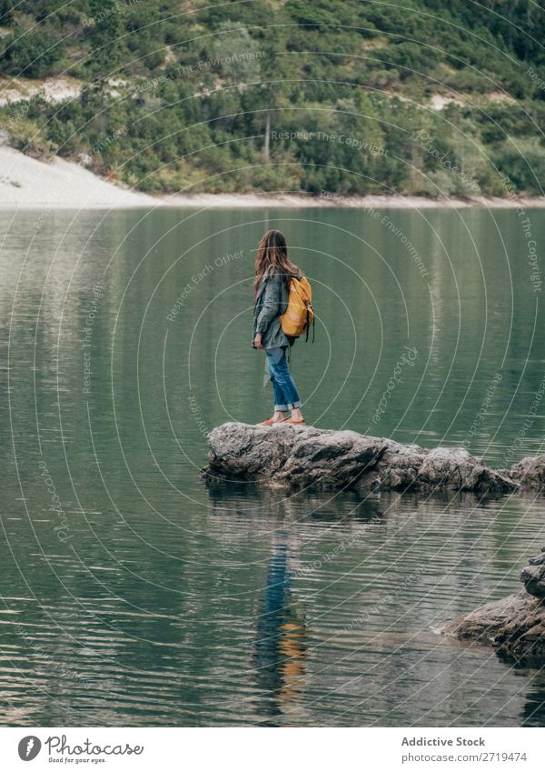 Female backpacker on stone in lake Woman Backpack Lake Mountain Tourism Landscape Action Freedom Tourist Adventure Nature Stone Posture Water Ripple