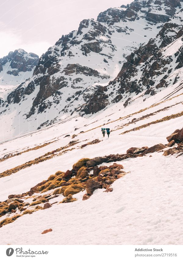 People walking on snowy slope of mountains Human being Mountain Tourism Winter Landscape Rock trekking Hiking Snow Lanes & trails Walking Vacation & Travel