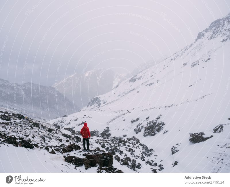 Anonymous person in snowy mountains Human being Mountain Tourism Winter Landscape Rock Ski-run Snow