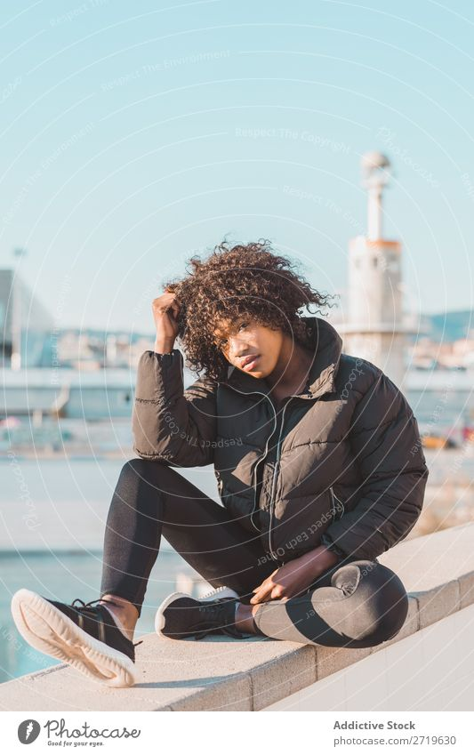 Stylish woman sitting on fence Woman Ethnic pretty Beautiful Youth (Young adults) City Park Sit Fence Style Easygoing Cool (slang) Portrait photograph