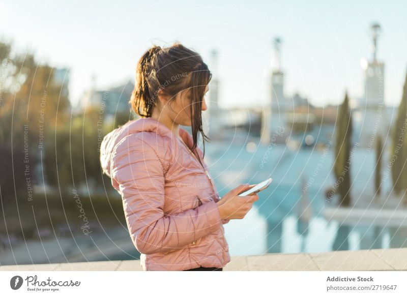 Pretty woman standing with smartphone on street Woman pretty PDA Park Happy Beautiful Telephone Youth (Young adults) Mobile Attractive Lifestyle Nature