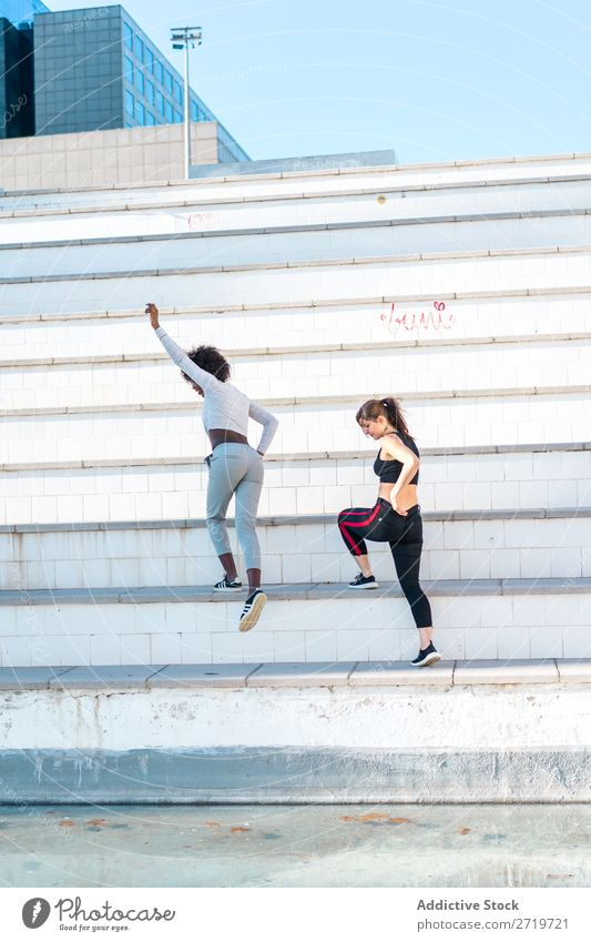 Pretty fit women jumping together Woman Athletic Together pretty Youth (Young adults) Cheerful Steps Jump Stretching Beautiful Sports multiethnic