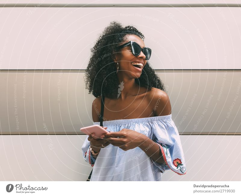 Cheerful black woman with mobile phone Woman Wall (building) Adults Easygoing PDA African Ethnic Cellphone Copy Space Youth (Young adults) Lifestyle pastel