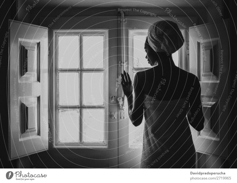 Woman wrapped in a towel looking by a vintage window. Window Black Adults Background picture Beauty Photography Attractive Considerate Ethnic Rear view Bedroom