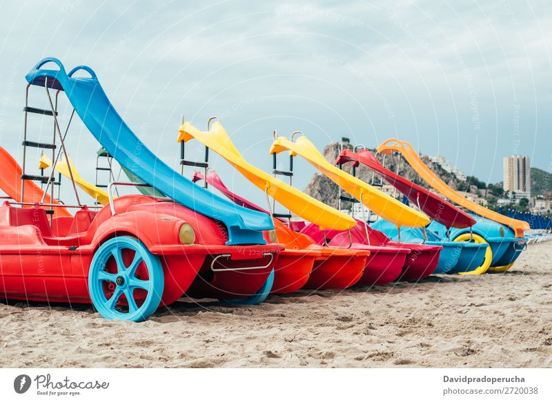 colorful Pedalos on the beach sand Beach Summer Watercraft Multicoloured Paddle Vacation & Travel Catamaran Red Background picture White Yellow Exterior shot