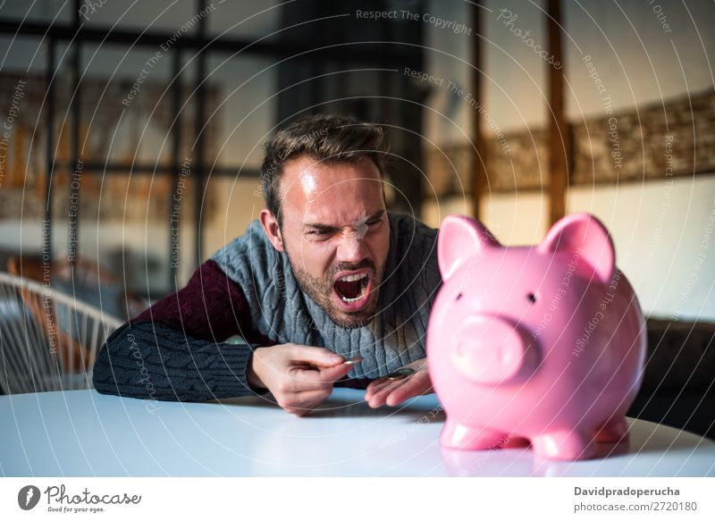 Unhappy man angry at his piggy bank Man Money box savings Crisis Sadness Anger Stress Emotions annoyed Scream trouble Expression frustrated Problem shouting