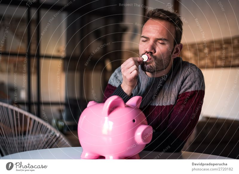 Young man kissing a coin with a piggy bank Man Money box savings Success Business cash Caucasian Coin Euro Beautiful Happy Cheerful investment wealth Kissing
