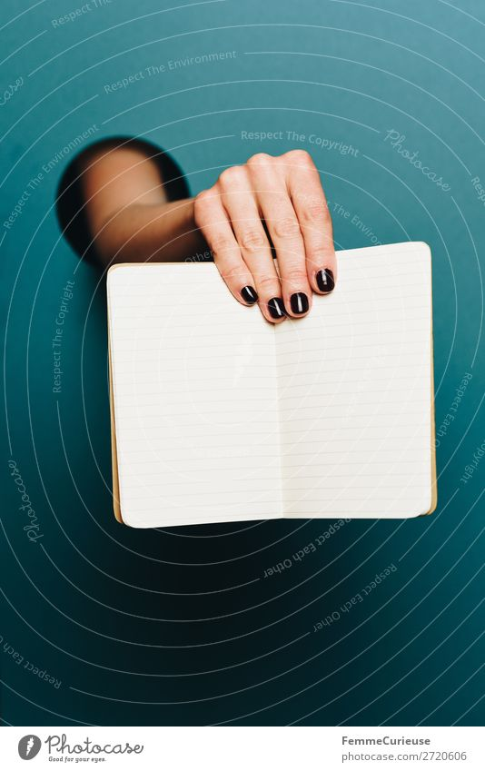 Hand of a woman holding a notebook in the camera Feminine 1 Human being Stationery Paper Creativity Notebook Lined Turquoise Nail polish Empty Write Design