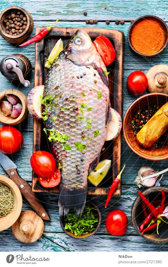 Fresh fish and food ingredients raw carp seafood raw fish fresh meal healthy cutting board cooking pepper tomato vegetable preparation spice salt diet uncooked