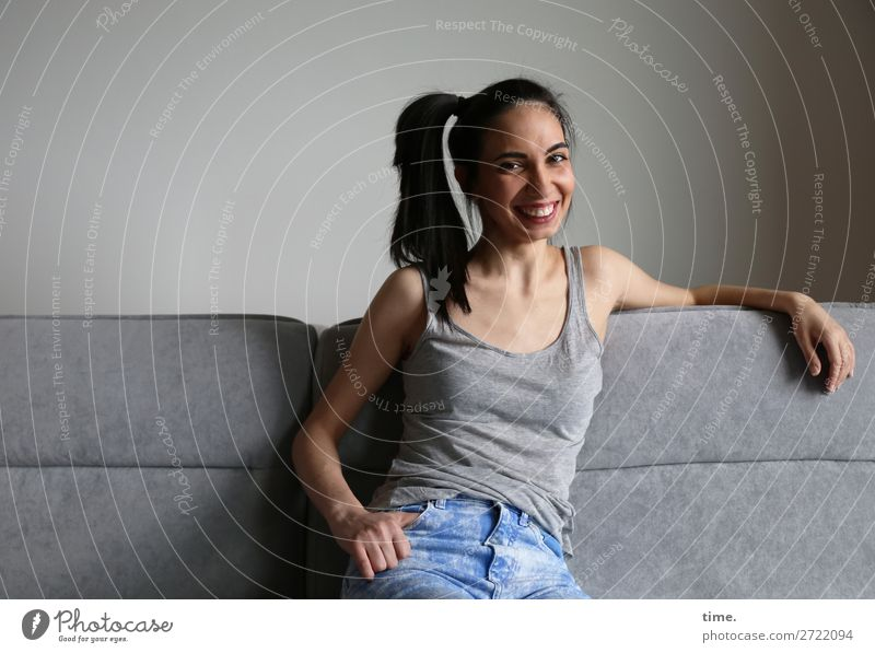 GizzyLovett Sofa Room Feminine Woman Adults 1 Human being T-shirt Jeans Black-haired Long-haired Braids To hold on Smiling Laughter Looking Sit Friendliness