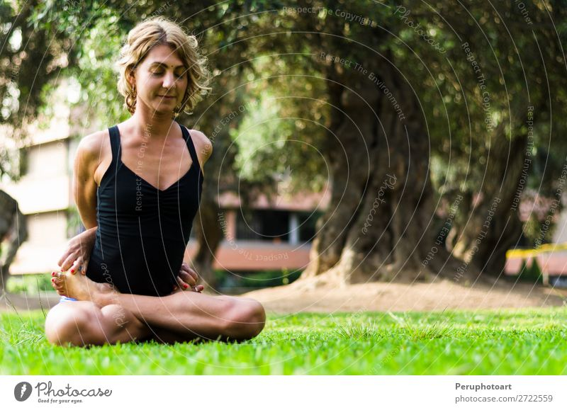 Woman practicing yoga .The Locked Lotus Pose Baddha Padmasana. Diet Lifestyle Beautiful Body Relaxation Meditation Leisure and hobbies Sports Yoga Adults Park
