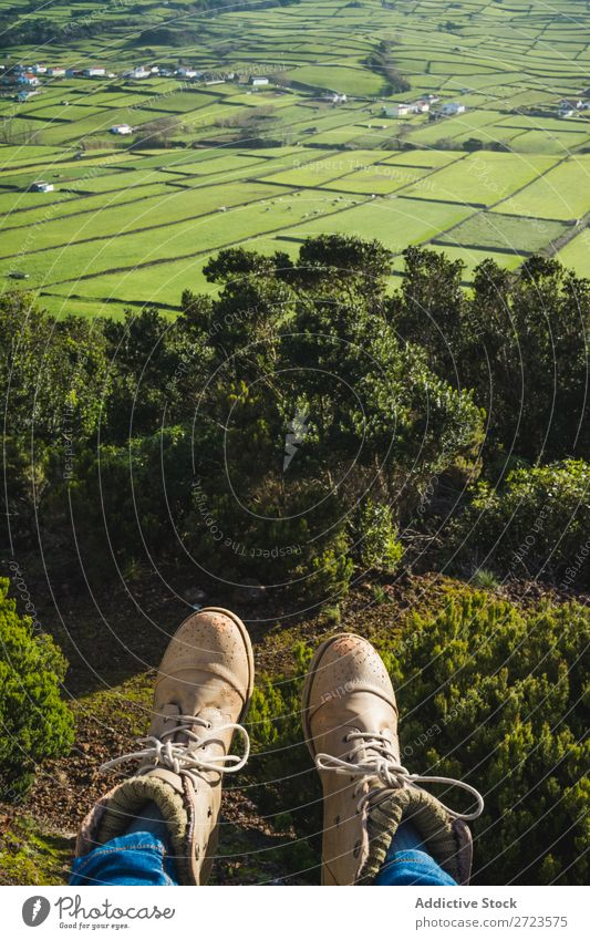 Person sitting on hill at fence Field Green Vantage point Nature Meadow Legs Footwear Grass Landscape Rural Summer Plant Azores Spring Lawn Landing Environment