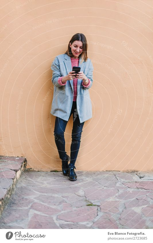 portrait outdoor of a young beautiful woman Lifestyle Style Happy Beautiful Cellphone Technology Internet Woman Adults Autumn Town Street Fashion Clothing