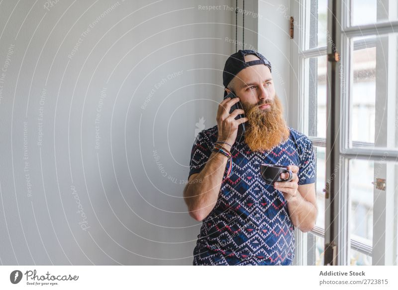 Man with cup and phone at window Home Relaxation Adults bearded PDA To talk To call someone (telephone) Cup Mug Hot Drinking Communication Window Easygoing