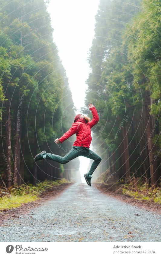 Man jumping on road in forest Tourist Nature bearded Jump Red Jacket Street Lanes & trails Forest Green Vacation & Travel Adventure Landscape Azores Hiking