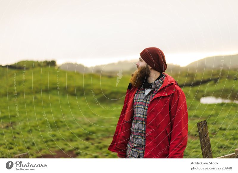 Dreamy bearded man in nature Tourist Field Green Landscape Nature Sky Summer Pensive Considerate Jacket Red Man Looking away Vacation & Travel Tourism Rural
