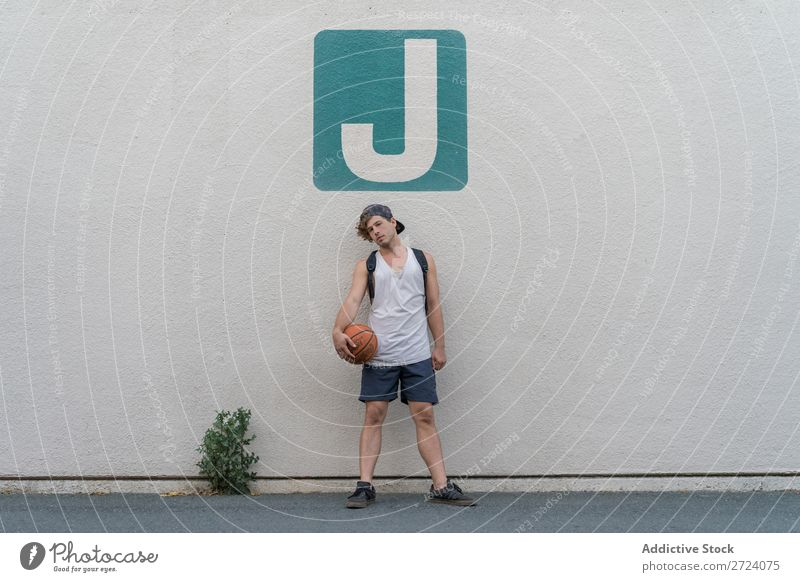 Man with basketball posing on wall Basketball Posture Street Sportswear Stand Lifestyle Relaxation