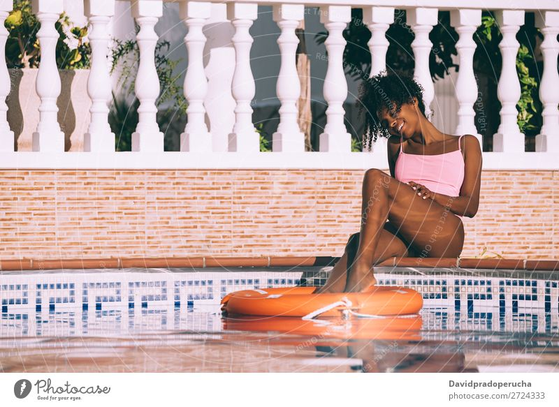 Black woman in a swimming pool with lifesaver Woman Ethnic Swimming pool Summer Lifeguard Sunbathing Barefoot Legs Pedicure Relaxation Skin tan Water