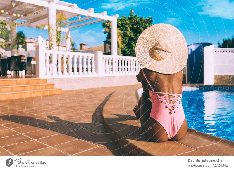 Black woman seating down in a swimming pool side Woman Ethnic Swimming pool Summer Sunbathing Vacation & Travel tan Horizontal tanning Relaxation Copy Space