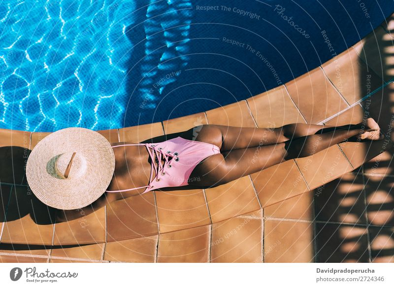 Black woman lying down in a swimming pool side Woman Ethnic Swimming pool Summer Sunbathing Vacation & Travel tan Horizontal tanning Relaxation Copy Space