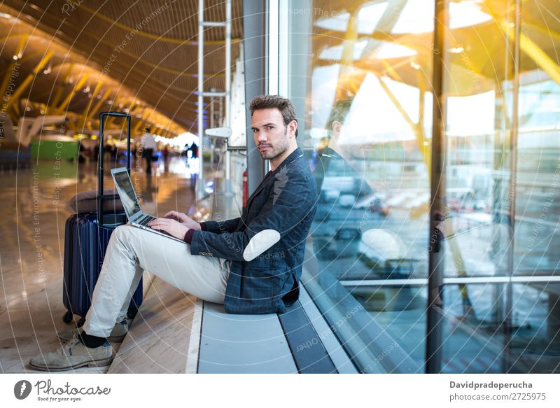 man sitting at the airport using laptop and mobile phone next to the window Airport Youth (Young adults) Smiling Wait Story Window Sun Sunrise Cellphone