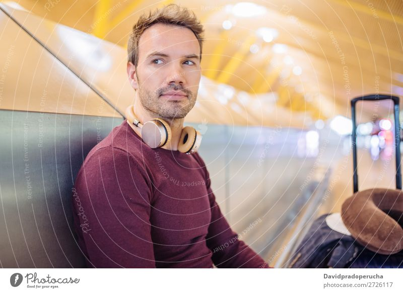 Young man waiting listening music and using mobile phone at the airport with a suitcase. Wait Airport Youth (Young adults) Smiling Caucasian Listening Music