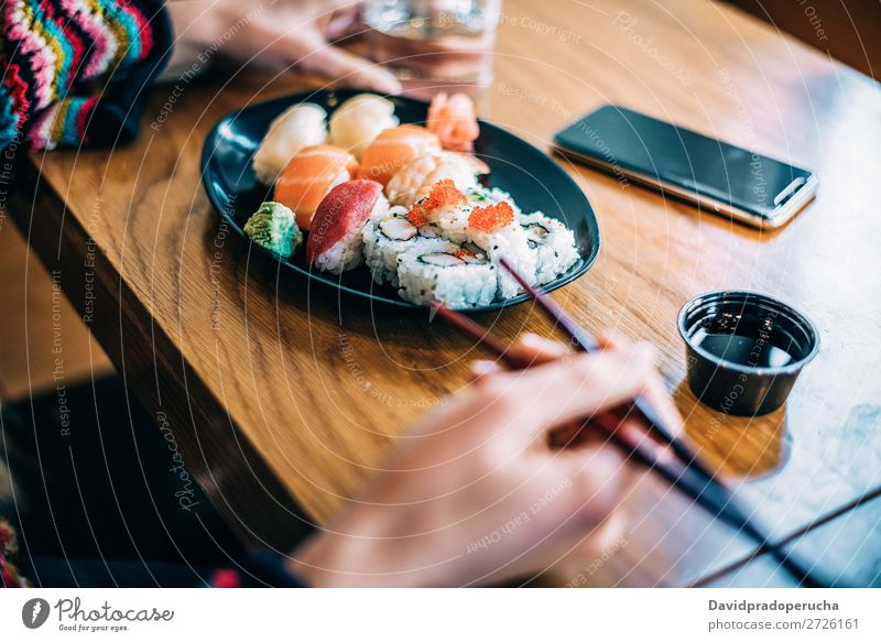 Crop woman eating sushi Sushi Woman Hand Food soy maki california roll Chopstick Roll Crops Unrecognizable Anonymous Close-up Portrait photograph Salmon