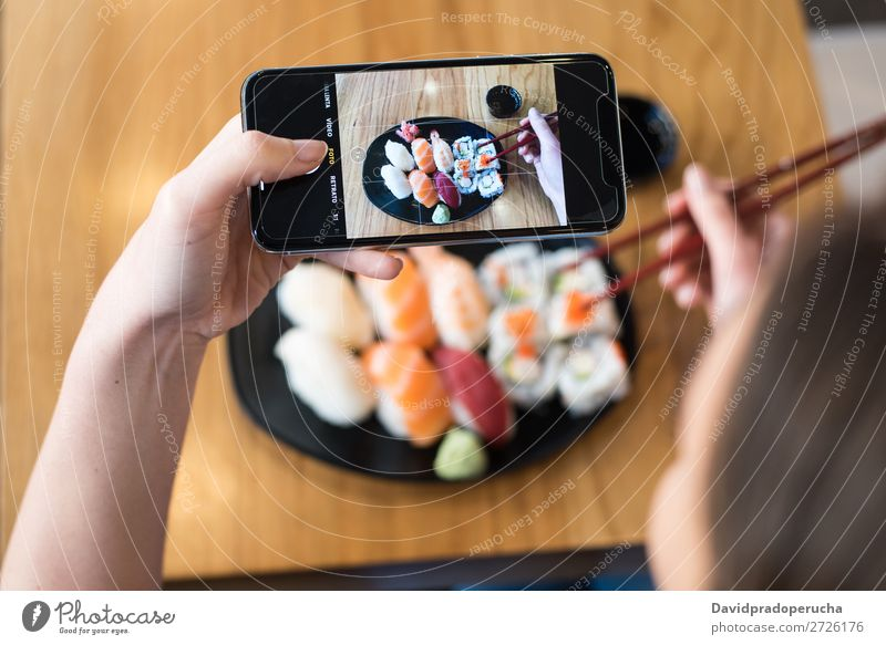 Top view of woman taking photo of sushi on the table Sushi Woman Photography PDA Mobile Telephone Shot Hand Food soy maki california roll Chopstick Roll Crops