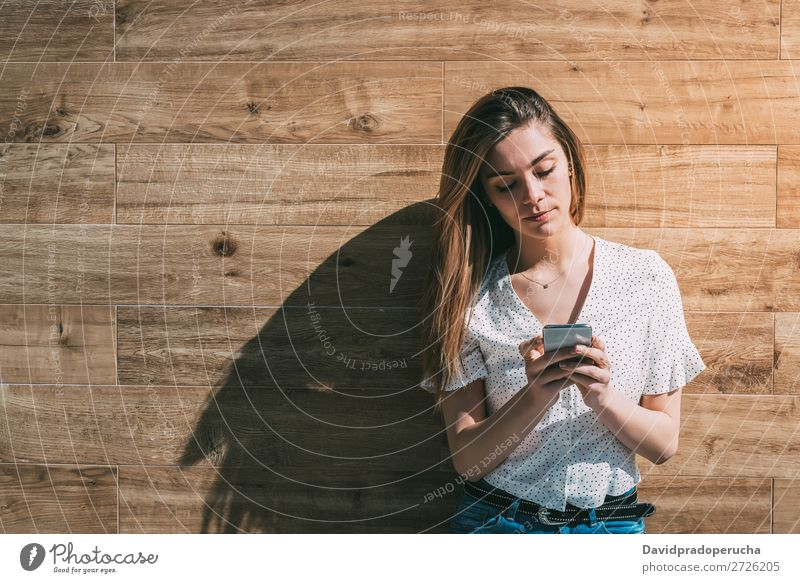 Happy woman using smartphone at a wooden wall Woman PDA Telephone Mobile Communication device Smiling Looking away Portrait photograph Wood Background picture