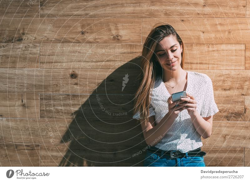 Happy woman using smartphone at a wooden wall Woman PDA Telephone Mobile Communication Smiling