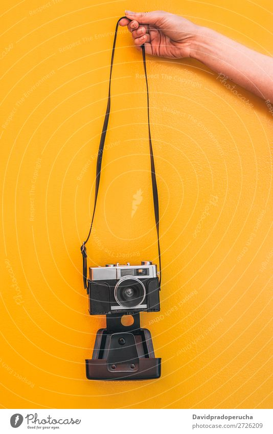 Hand holding a Vintage camera isolated at orange wall Arm Camera Orange Wall (building) Retro Old Isolated Studio shot Hold Leisure and hobbies Illustration